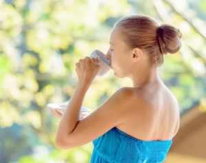 Young woman drinking coffee on morning terrace